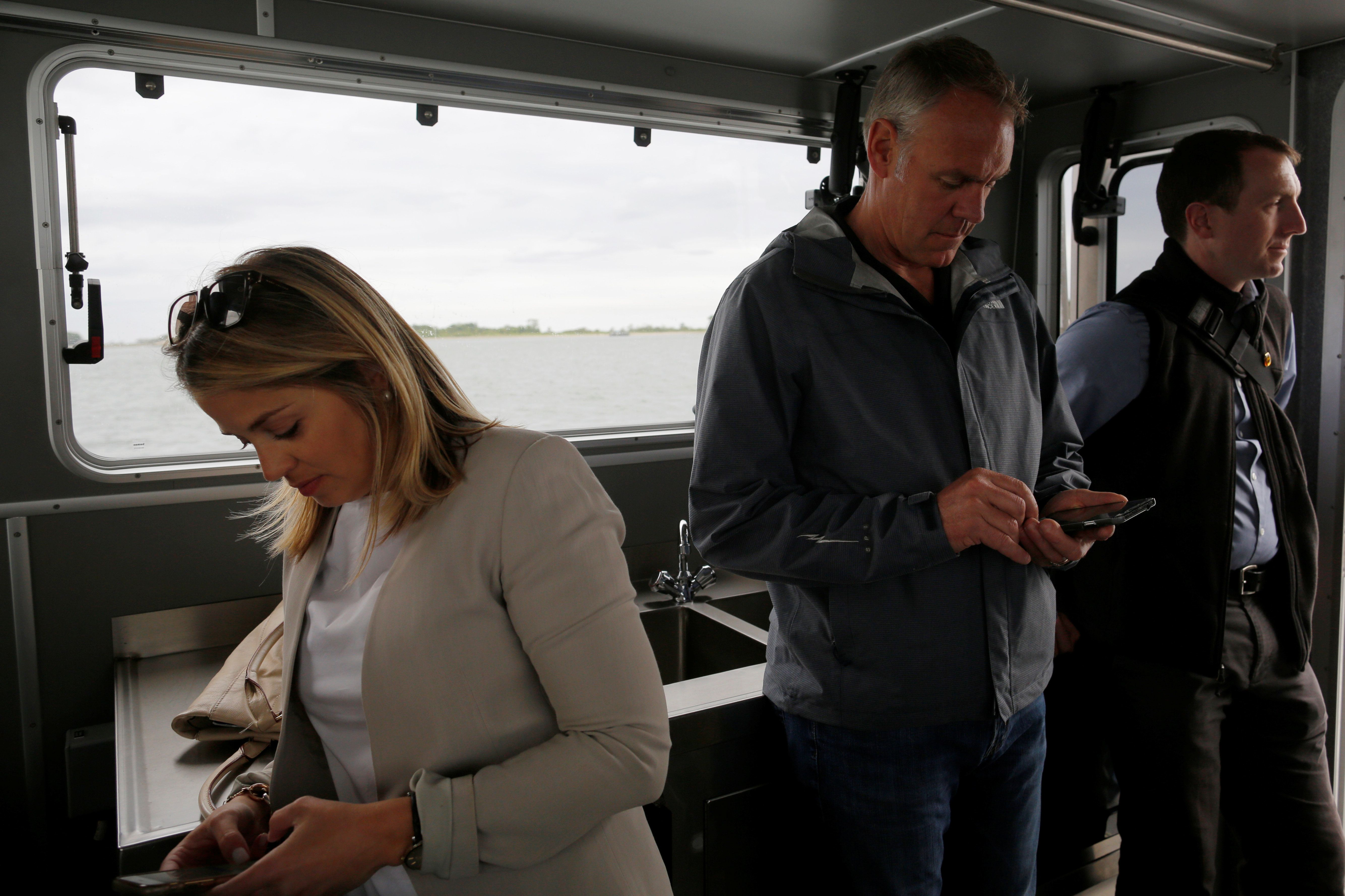 U.S. Interior Secretary Ryan Zinke (C) checks his mobile phone after a visit to Georges Island, part of his National Monuments review process, in Boston Harbor, Massachusetts, U.S., June 16, 2017.  Picture taken June 16, 2017.   REUTERS/Brian Snyder