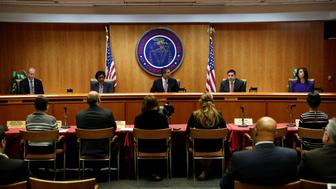 Chairman Ajit Pai (C) leads a vote on the repeal of so called net neutrality rules at the Federal Communications Commission in Washington, U.S., December 14, 2017. REUTERS/Aaron P. Bernstein