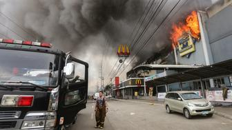 This photo taken on December 23, 2017 shows a firefighter standing in front of a burning shopping mall in Davao City on the southern Philippine island of Mindanao.  Thirty-seven people were believed killed in a fire that engulfed a shopping mall in the southern Philippine city of Davao, local authorities said on December 24. / AFP PHOTO / MANMAN DEJETO        (Photo credit should read MANMAN DEJETO/AFP/Getty Images)