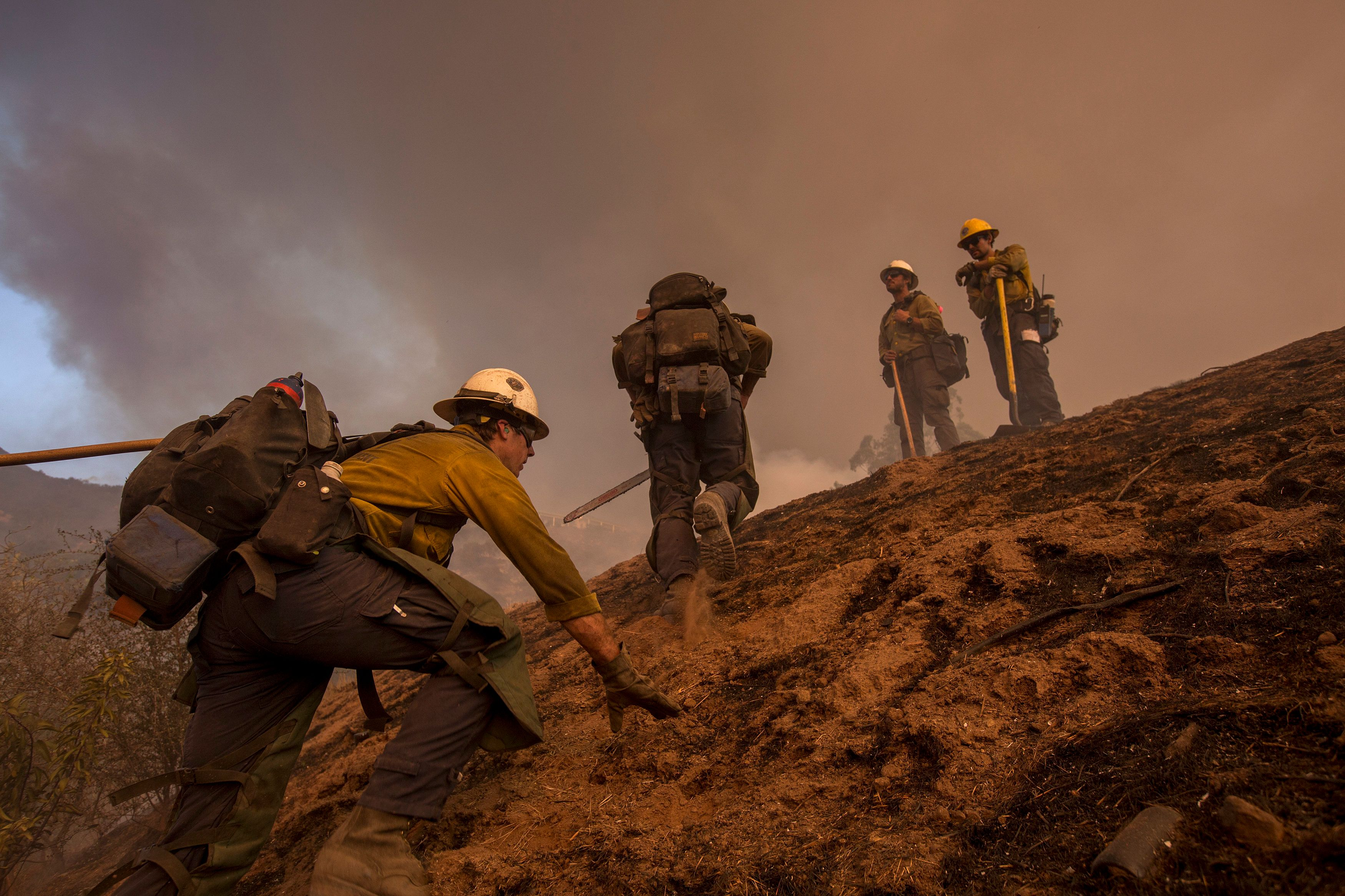 MONTECITO, CA - DECEMBER 16: A Hot Shot crew climbs a steep hill while cutting a line among homes at the Thomas Fire on December 16, 2017 in Montecito, California. The National Weather Service has issued red flag warnings of dangerous fire weather in Southern California for the duration of the weekend. Prior to the weekend, Los Angeles and Ventura counties had 12 consecutive days of red flag fire warnings, the longest sustained period of fire weather warnings on record. The Thomas Fire is currently the fourth largest California fire since records began in 1932, growing to 400 square miles and destroying more than 1,000 structures since it began on December 4. (Photo by David McNew/Getty Images)
