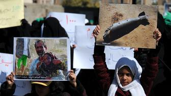 SANA'A, YEMEN – DECEMBER 21: Yemeni children hold pictures of victims of airstrikes as they take part in a rally staged against the ongoing 1000-day war on Yemen by the Saudi-led coalition outside the United Nations Office on December 21, 2017 in Sana'a, Yemen. (Photo by Mohammed Hamoud/Getty Images)