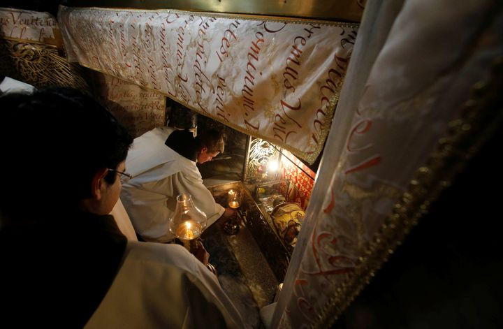 Clergymen attend a Christmas midnight mass at the Church of the Nativity in the West Bank city of Bethlehem on December 25, 2
