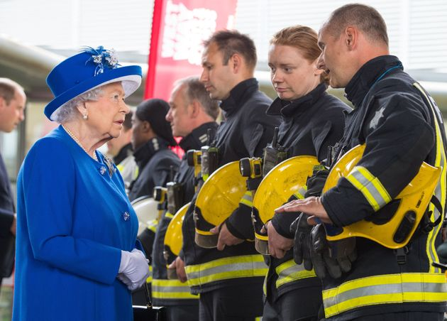 The Queen meets firefighters during a visit to the Westway Sports Centre after fire engulfed the Grenfell...
