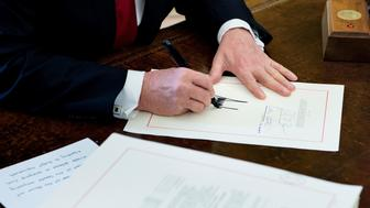 United States President Donald J. Trump signs the Tax Cut and Reform Bill in the Oval Office at The White House in Washington, DC on December 22, 2017.  / AFP PHOTO / Brendan Smialowski        (Photo credit should read BRENDAN SMIALOWSKI/AFP/Getty Images)