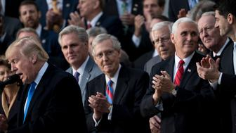 House Majority Leader Representative Kevin McCarthy (R-CA) (2L), Senate Majority Leader Senator Mitch McConnell (R-KY) (C), US Vice President Mike Pence (2R), Speaker of the House Paul Ryan (R-WI) (R) and others listen while US President Donald Trump speaks about newly passed tax reform legislation during an event December 20, 2017 in Washington, DC. Trump hailed a 'historic' victory Wednesday as the US Congress passed a massive Republican tax cut plan, handing the president his first major legislative achievement since taking office nearly a year ago. / AFP PHOTO / Brendan Smialowski        (Photo credit should read BRENDAN SMIALOWSKI/AFP/Getty Images)