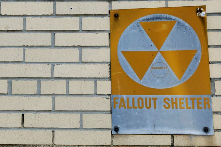 A yellow nuclear fallout shelter sign hangs on a building in Brooklyn.