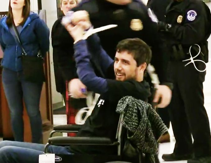 Ady Barkan raises his fists in triumph after getting arrested while protesting the tax bill on Dec. 18, 2017, his 34th birthd