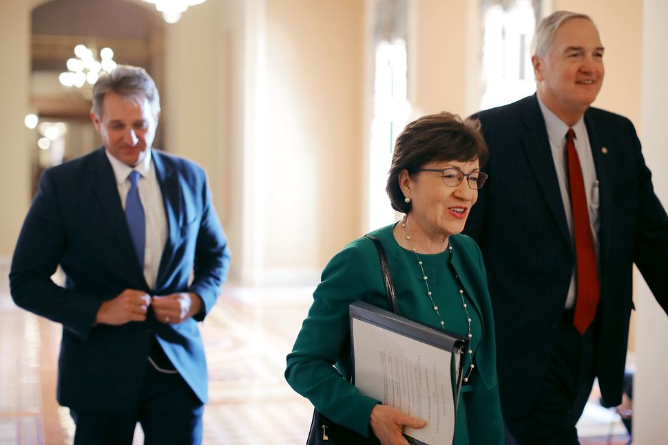 Sen. Jeff Flake (R-Ariz.), left, and Sen. Susan Collins (R-Maine), center, did not change their votes after meeting with Bark