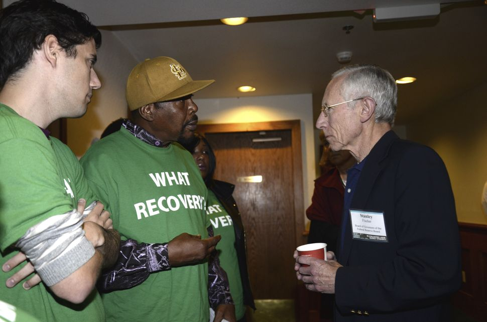 Reggie Rounds of Ferguson, Missouri (center), speaks to Federal Reserve Vice Chair Stanley Fischer (right), as Ady Barkan (le