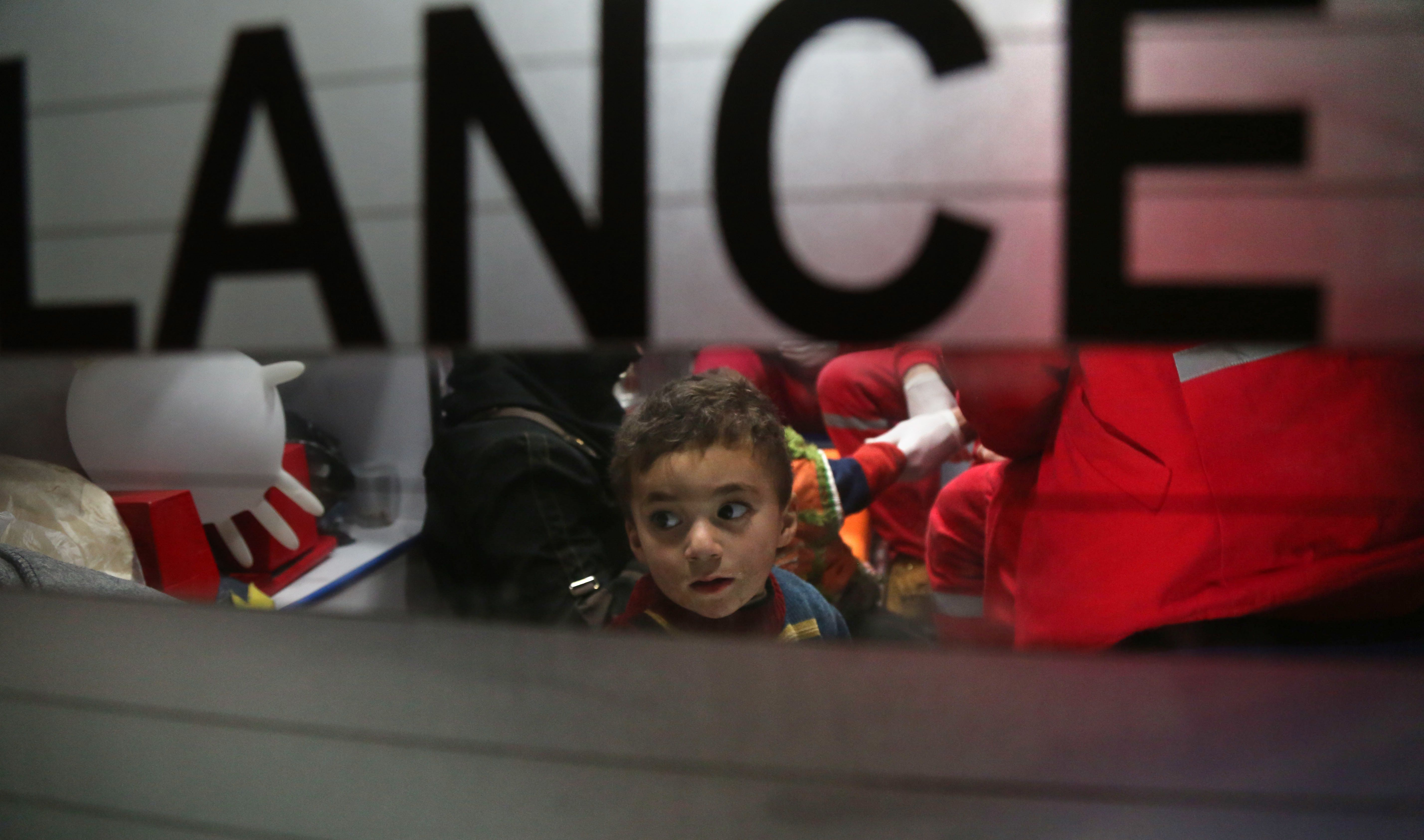 A Syrian child sits in an ambulance during an evacuation operation by the International Committee of the Red Cross in Douma in the eastern Ghouta region on the outskirts of the capital Damascus late on December 26, 2017. Aid workers have begun evacuating emergency medical cases from Syria's besieged rebel bastion of Eastern Ghouta, the International Committee of the Red Cross said, after months of waiting during which the UN said at least 16 people had died. Eastern Ghouta is one of the last remaining rebel strongholds in Syria and has been under a tight government siege since 2013, causing severe food and medical shortages for some 400,000 residents. / AFP PHOTO / Amer ALMOHIBANY        (Photo credit should read AMER ALMOHIBANY/AFP/Getty Images)