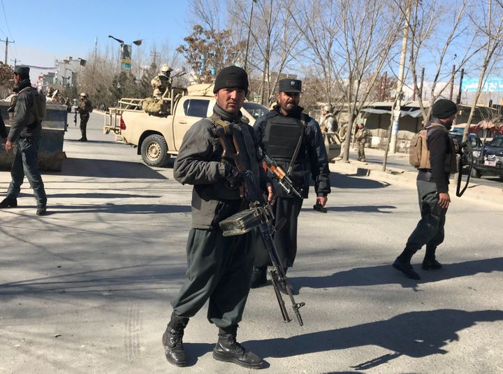 Police officers stand guard at thesite of the blastat the Afghan Voice news agency in Kabul.