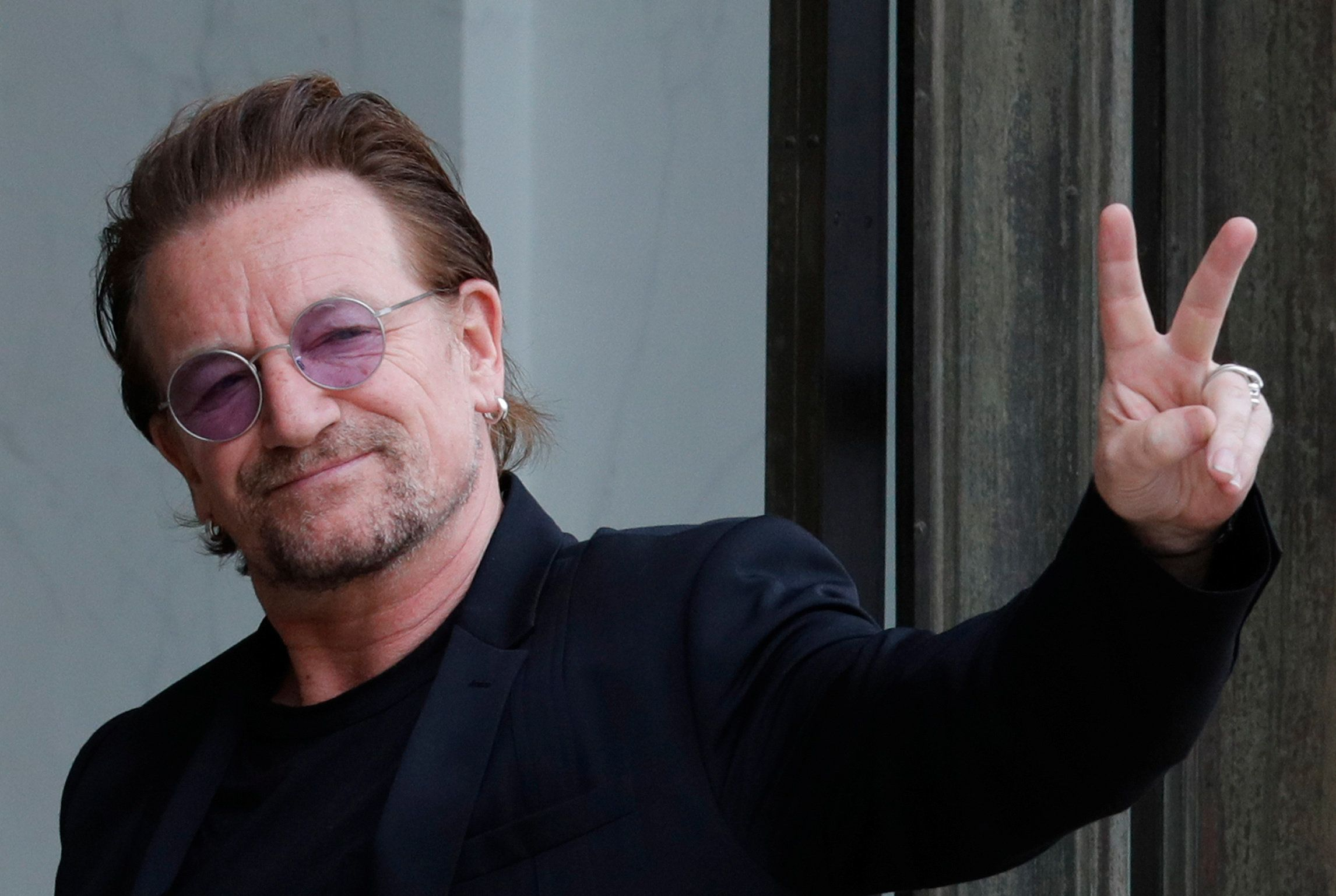 Singer Bono of Irish band U2 and co-founder of ONE organization waves as he arrives at the Elysee Palace in Paris, France, July 24, 2017.     REUTERS/Philippe Wojazer