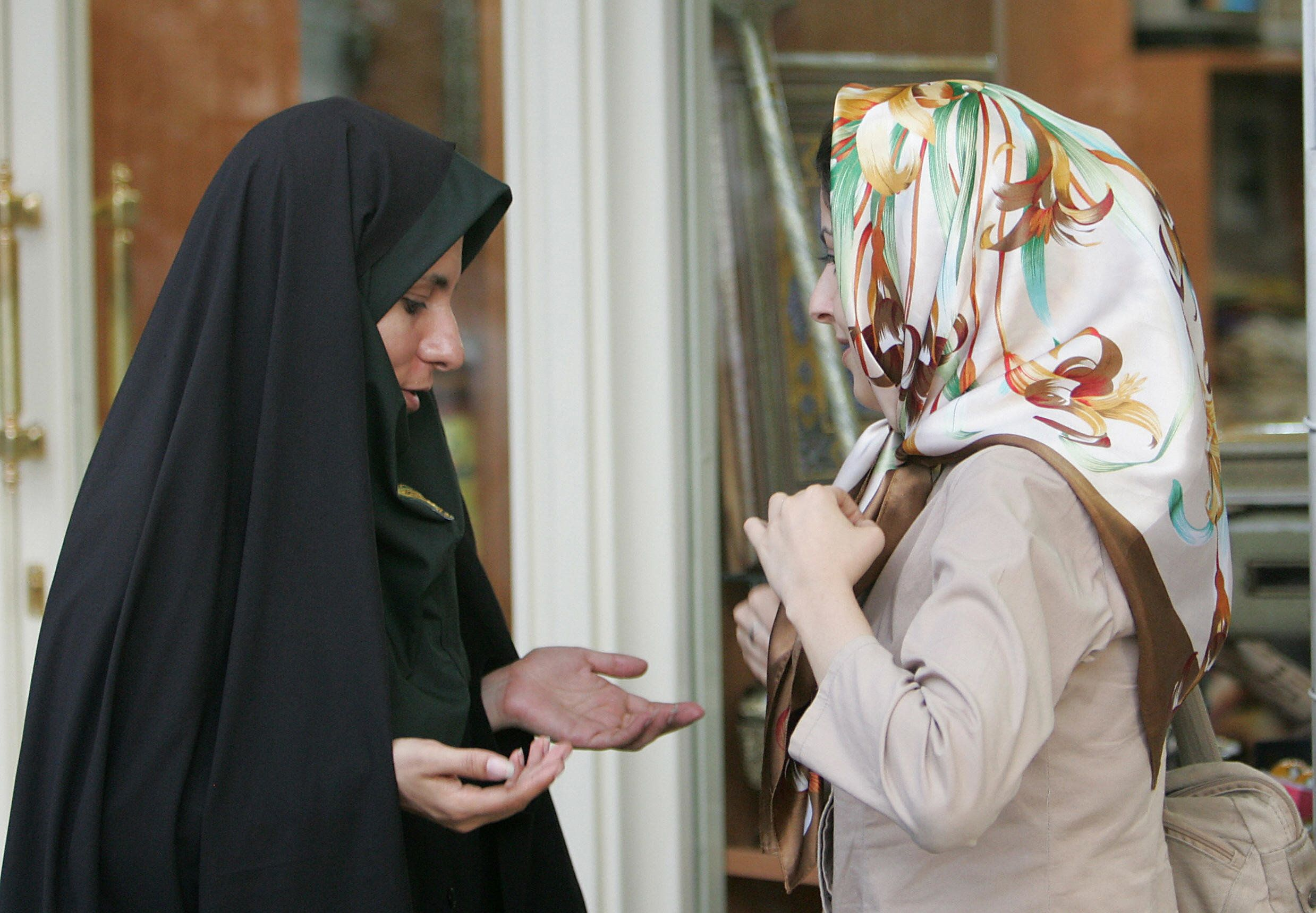Tehran, IRAN: A female Iranian police officer (L) speaks with a woman regarding her clothing during a crackdown to enforce Islamic dress code in Tehran, 23 July 2007. Iran yesterday launched a new wave of a moral crackdown against women who 'dress like models' and men whose hairstyles are deemed unIslamic, police said. AFP PHOTO/BEHROUZ MEHRI (Photo credit should read BEHROUZ MEHRI/AFP/Getty Images)