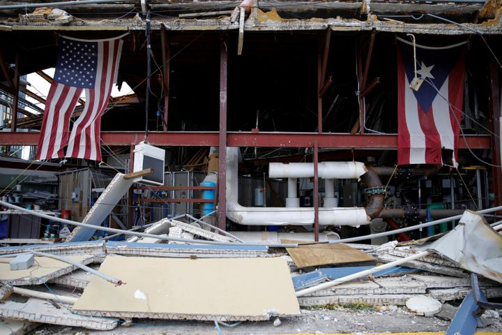U.S. and Puerto Rico flags hang on a hurricane-damaged church in Carolina, Puerto Rico, on Sept. 26.