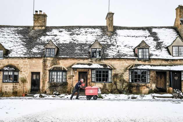 A postman pushes his trolley past snow-covered cottages on the High Street in Broadway,