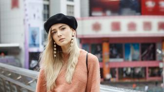 A beautiful young blonde woman dressed in a large warm pink sweater with a black beret and gorgeous earrings. She goes through a big spectacular Chinese city in autumn and enjoying every moment.