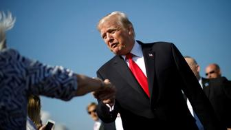 U.S. President Donald Trump shakes hands with supporters as he arrives at West Palm Beach international airport in West Palm Beach, Florida, U.S., December 22, 2017. REUTERS/Carlos Barria