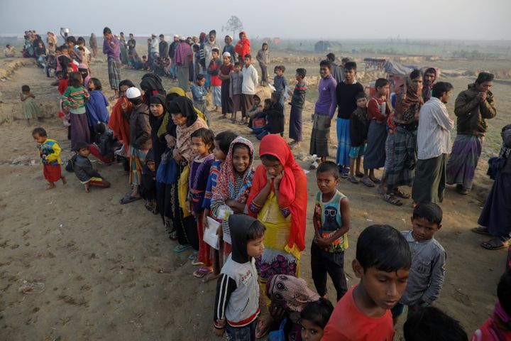 Rohingya refugees wait for a rice delivery at a Bangladesh camp in December.
