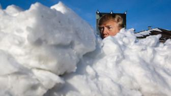 Snow piles up on the ground near a picture of U.S. Republican presidential candidate Donald Trump displayed outside a house in West Des Moines, Iowa, February 3, 2016. REUTERS/Scott Morgan