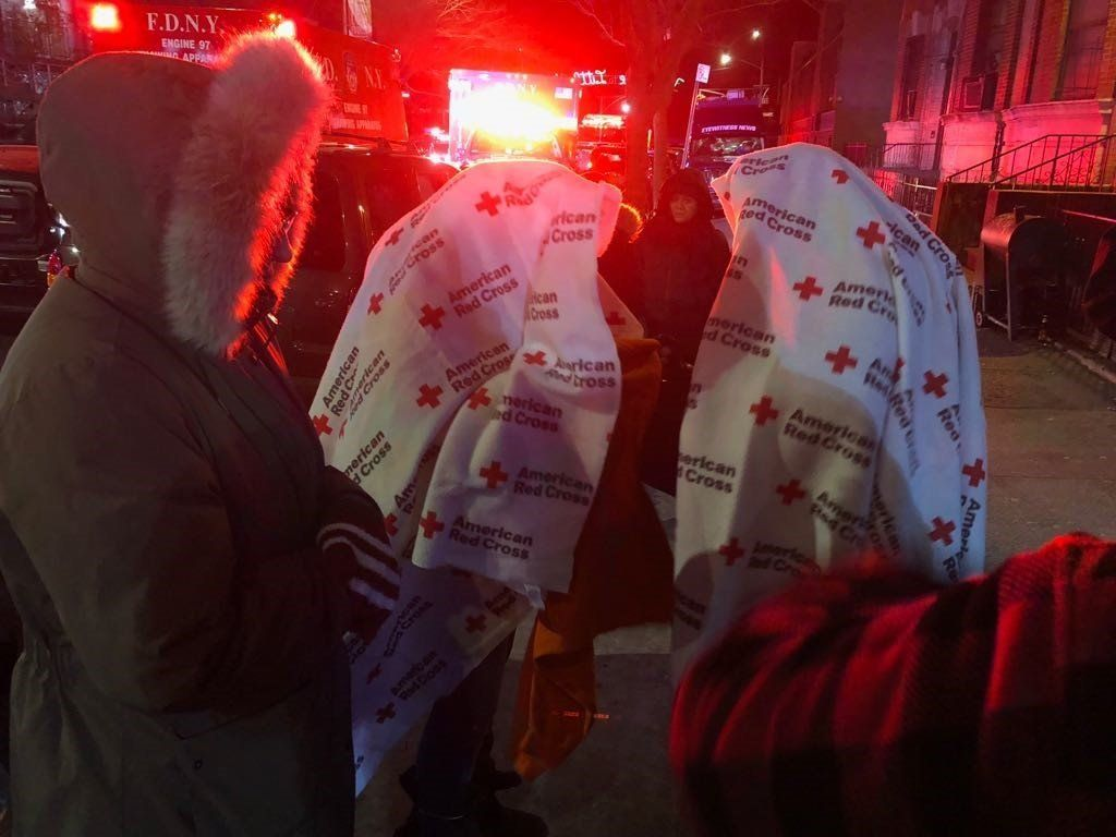 Displaced residents stand outside in freezing temperatures while firefighters fight one of the worst blazes New York City has