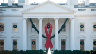 A red ribbon in recognition of World AIDS Day hangs from the North Portico of the White House in Washington, DC, December 1, 2017. / AFP PHOTO / SAUL LOEB        (Photo credit should read SAUL LOEB/AFP/Getty Images)