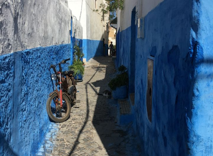 Narrow street with blue walls in Morocco.