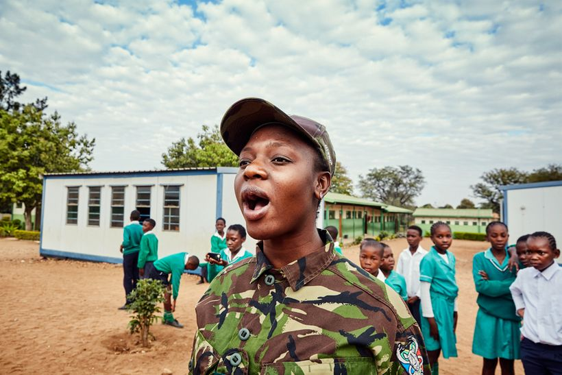 Black Mamba scout Nkateko Mzimba demonstrates how to shout orders to a group of school children, Foskor Primary School, South