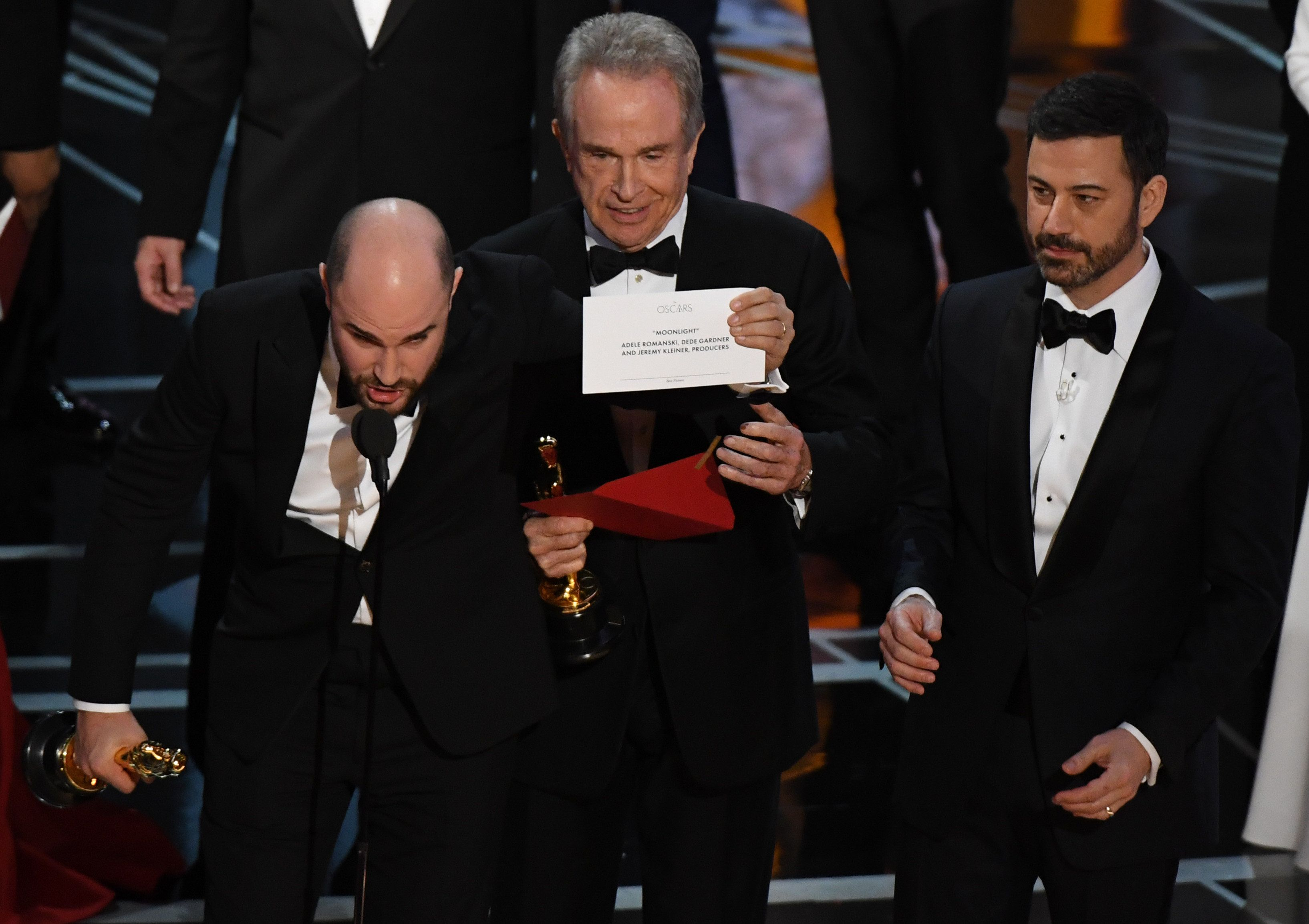 'La La Land' producer Jordan Horowitz (L) shows the card saying 'Moonlight' won the best picture as actor Warren Beatty  (C), and Host Jimmy Kimmel look on at the 89th Oscars on February 26, 2017 in Hollywood, California. / AFP / Mark RALSTON        (Photo credit should read MARK RALSTON/AFP/Getty Images)
