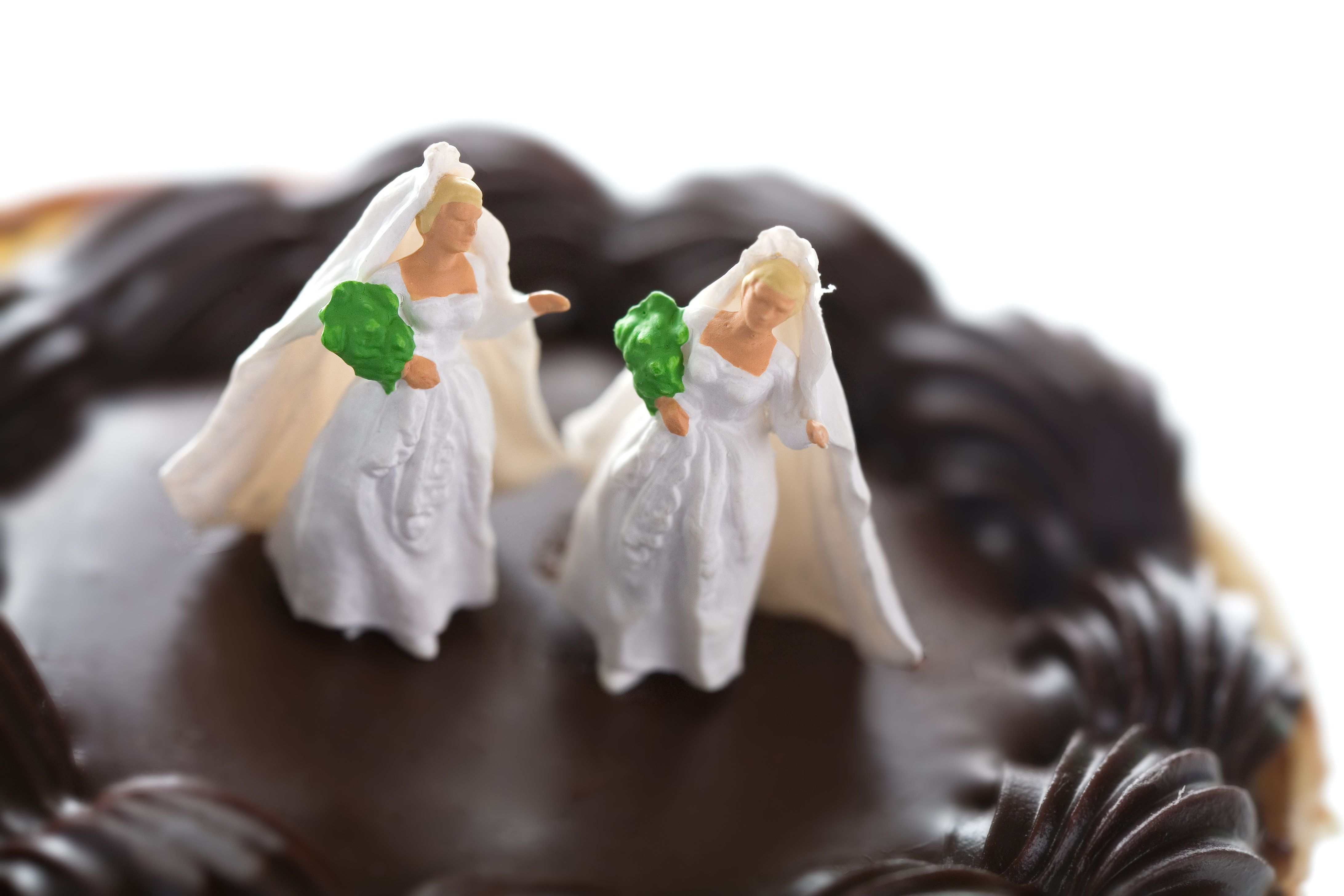 Tiny wedding figures atop a small heart-shaped pastry. These figures are extremely small, about half an inch tall. Conceptual; extremely shallow depth of field.