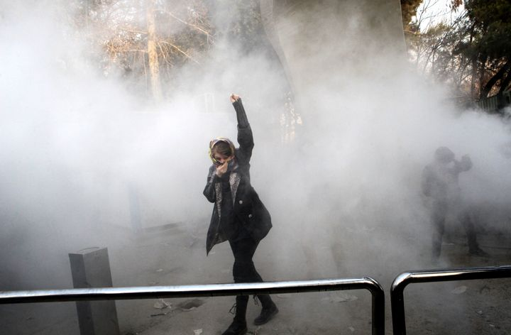 An Iranian woman raises her fist amid the smoke of tear gas at the University of Tehran during a protest driven by anger over economic problems on December 30, 2017.