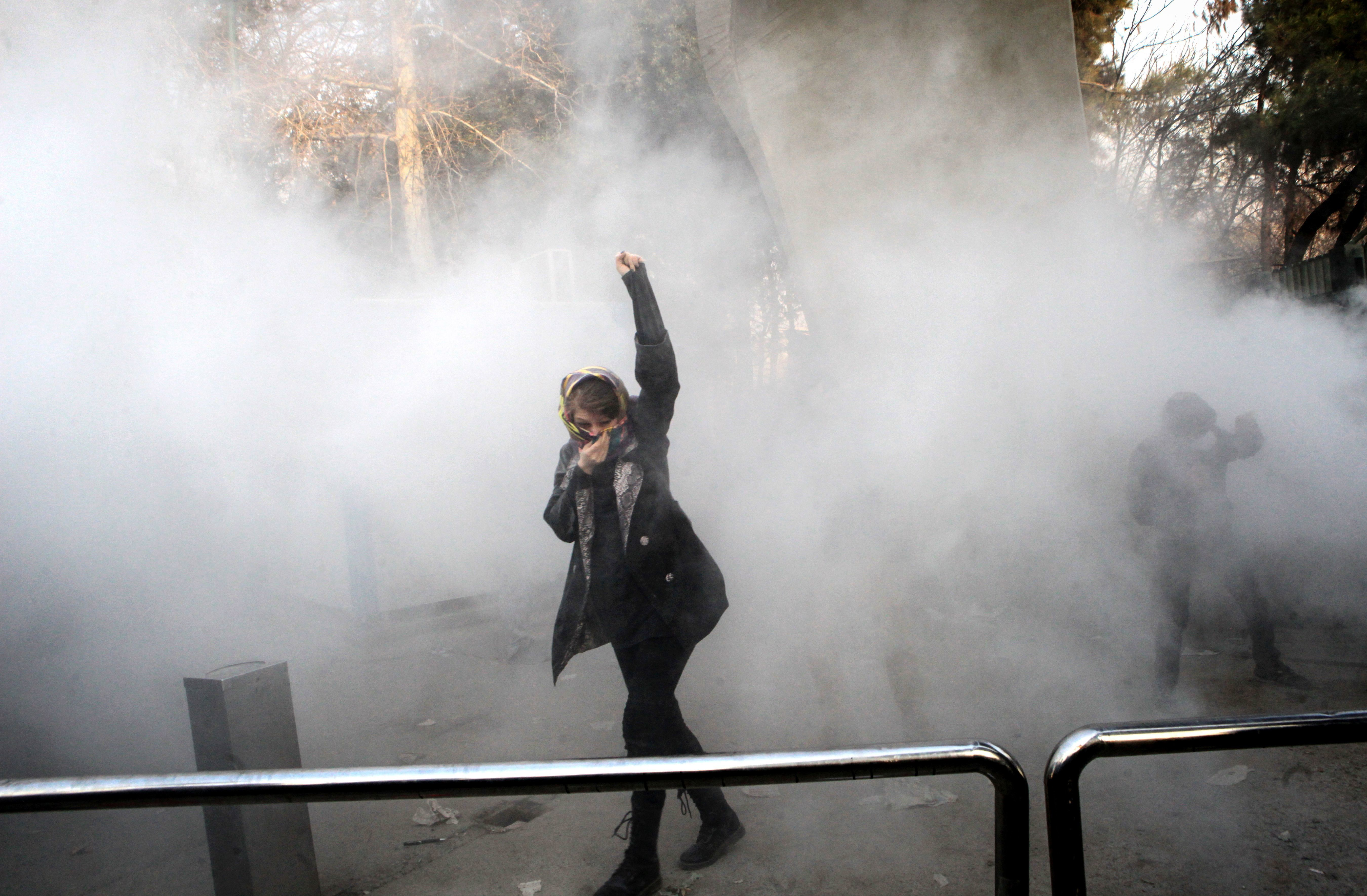 An Iranian woman raises her fist amid the smoke of tear gas at the University of Tehran during a protest driven by anger over