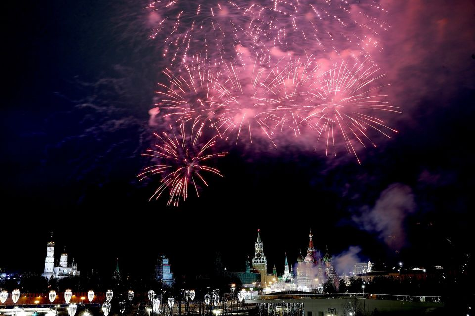 Fireworks light up the sky over the Bolshoy Kamenny Bridge with the Red Square and Kremlin Palace in...