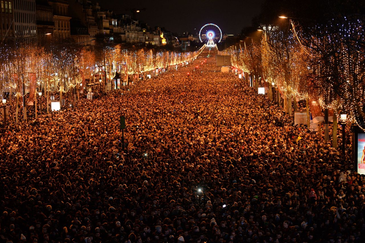 New Year revelers gather on the Champs-Elysees avenue in Paris on December 31, 2017.