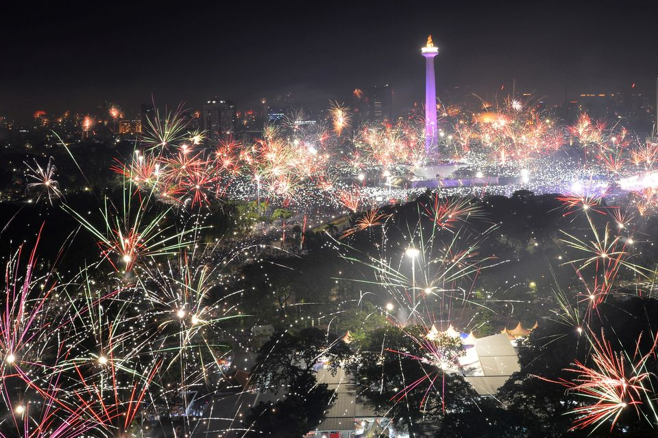 Fireworks explode around the National Monument during New Year's celebrations in Jakarta, Indonesia on...