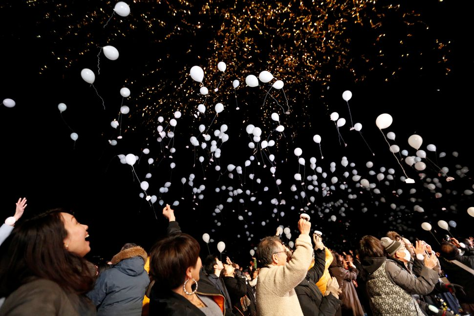 People release balloons as they take part in a New Year's countdown event in Tokyo, Japan on January 1, 2018.