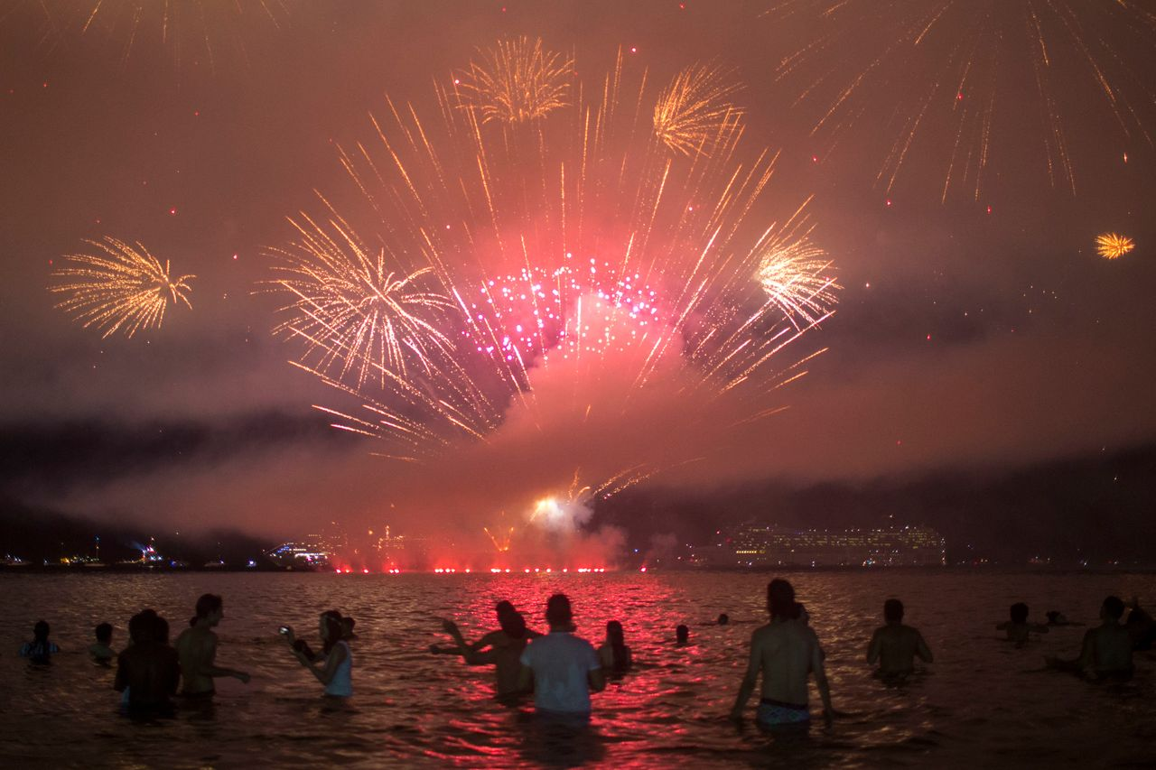 People watch fireworks during New Year's celebrations at Copacabana beach in Rio de Janeiro on January 1, 2018.