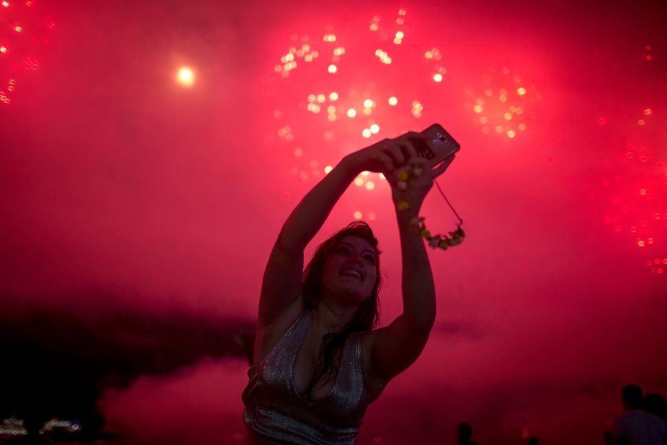 A woman takes a selfie during New Year's celebrations at Copacabana beach in Rio de Janeiro on January 1, 2018.