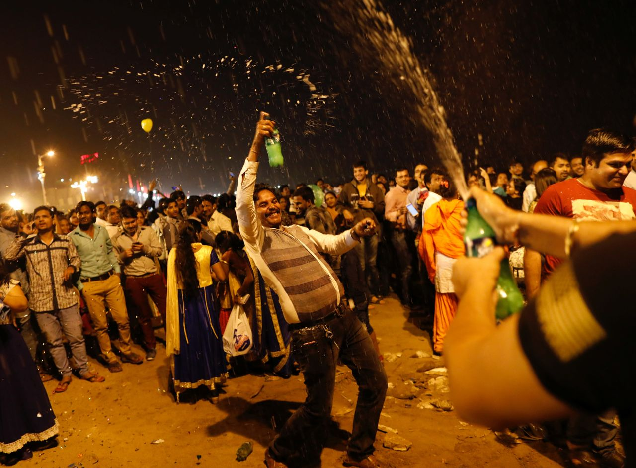 People dance during New Year's celebrations on a beach in Mumbai, India on January 1, 2018.