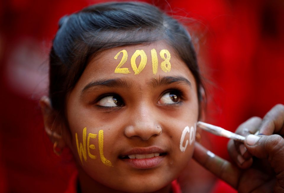 A schoolgirl reacts as she gets her face painted during New Year's celebrations at her school in Ahmedabad,