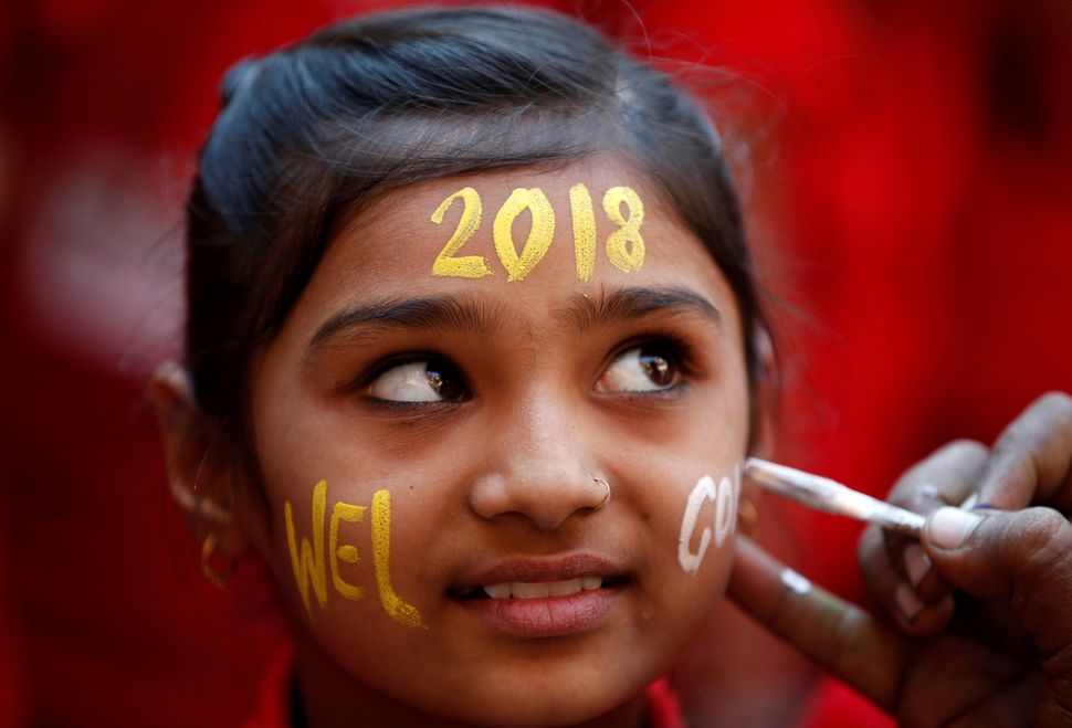 A schoolgirl reacts as she gets her face painted during New Year's celebrations at her school in Ahmedabad, India.