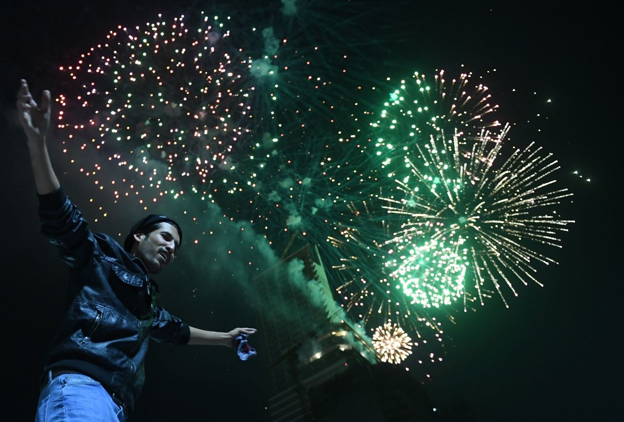 A Pakistani man dances on a street next to fireworks as he celebrates the new year in the port city of Karachi early on January 1, 2018.