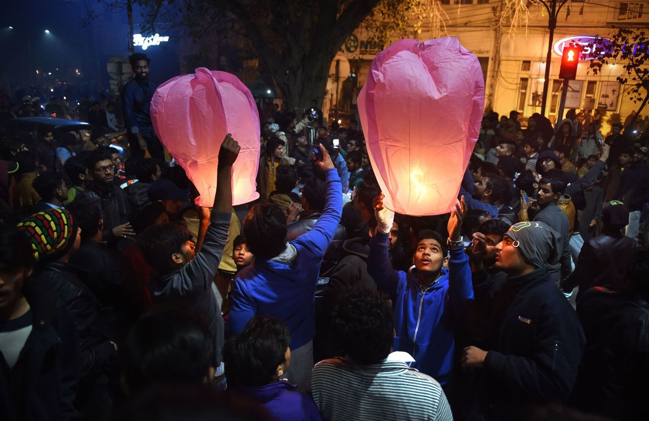 Pakistani people prepare to release lanterns as they gather to celebrate the new year in Lahore on January 1, 2018.