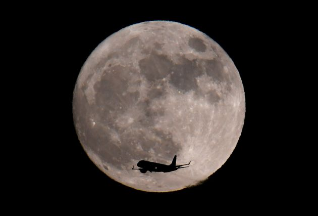 A passenger plane, with the moon seen behind, makes its final landing approach towards Heathrow Airport...