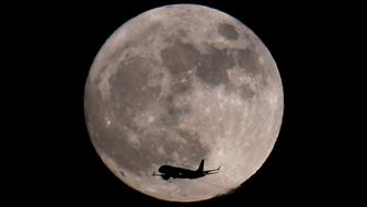 A passenger plane, with a 'supermoon' full moon seen behind, makes its final landing approach towards Heathrow Airport in London, Britain, January 1, 2018.  REUTERS/Toby Melville     TPX IMAGES OF THE DAY