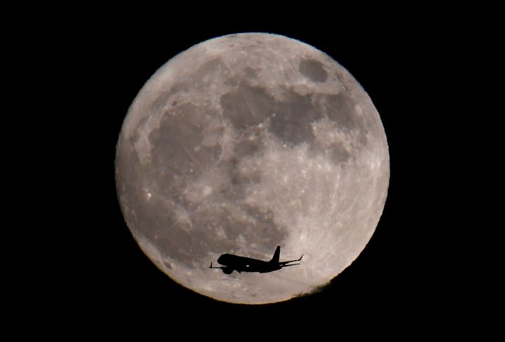 A passenger plane, with the moon seen behind, makes its final landing approach towards Heathrow Airport in London.