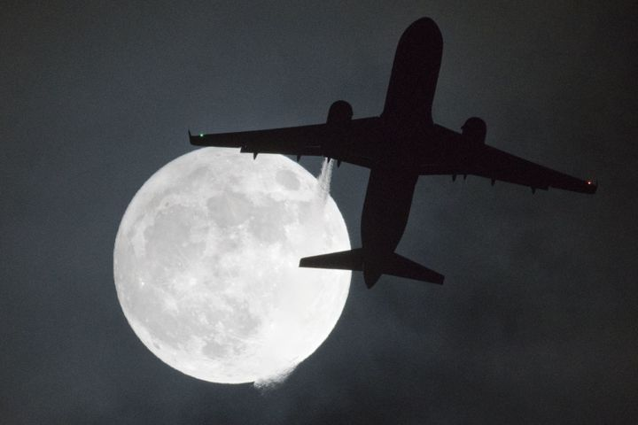 An airplane passes in front of the moon on its approach to London's Heathrow Airport.