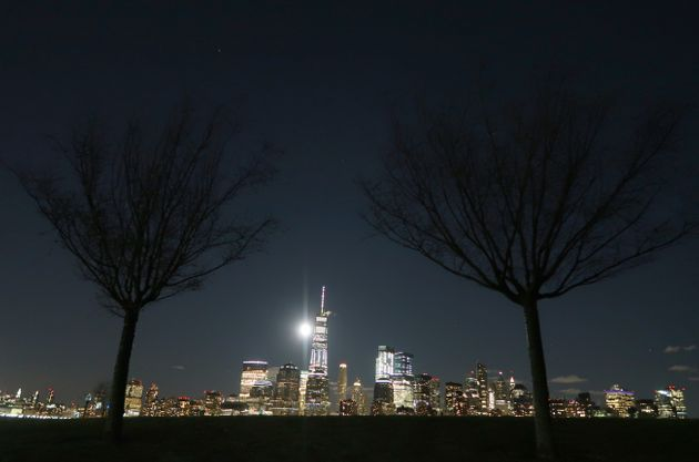 The supermoon rises behind the skyline of lower Manhattan and One World Trade Center in New York