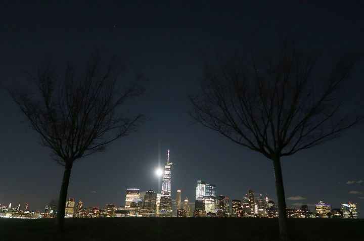 The supermoon rises behind the skyline of lower Manhattan and One World Trade Center in New York City.