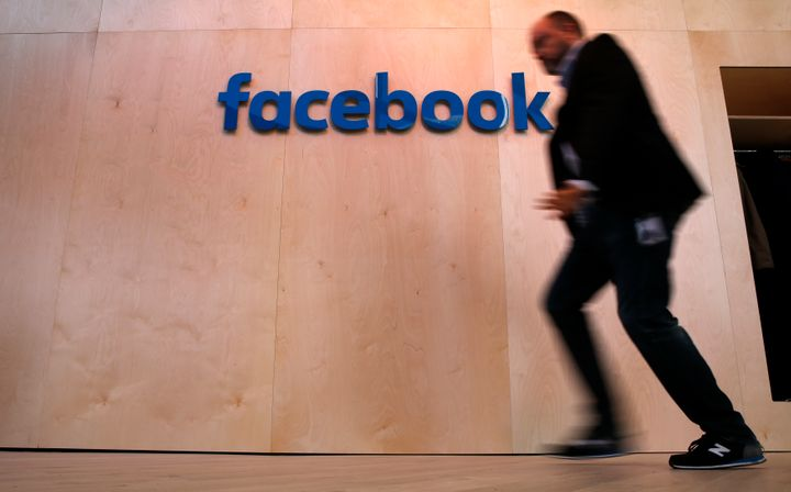 A man walks in front of the Facebook logo at the Facebook Innovation Hub in Berlin.