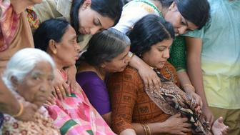 Sunayana Dumala (R), wife of killed Indian engineer Srinivas Kuchibhotla, who was shot dead in the US state of Kansas, is consoled by family members prior to performing the last rites at his funeral in Hyderabad on February 28, 2017. Thousands of Indians visit the United States every year for work or study, and the killing of 32-year-old engineer Srinivas Kuchibhotla in a Kansas bar last week has caused shockwaves around the country. / AFP / NOAH SEELAM        (Photo credit should read NOAH SEELAM/AFP/Getty Images)